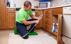 man working on kitchen plumbing