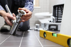 man working on plumbing with level